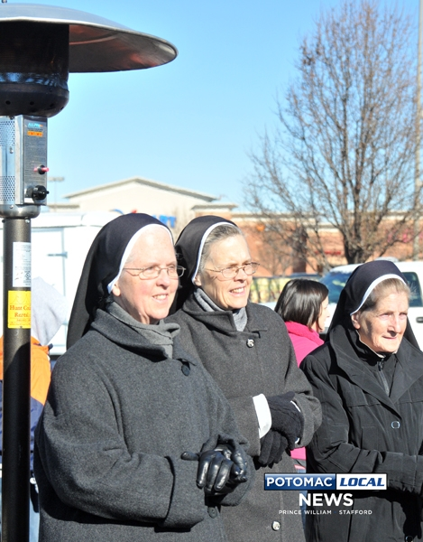Three Sisters huddled under a portable heaterto stay warm as they watched the festivities.
