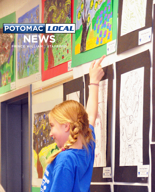 9 year old Lexi Bove, from Grafton Elementary, proudly points out her painting to her parents.
