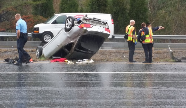 A witness said the driver of an overturned car crawled out and spoke with crash investigators.
