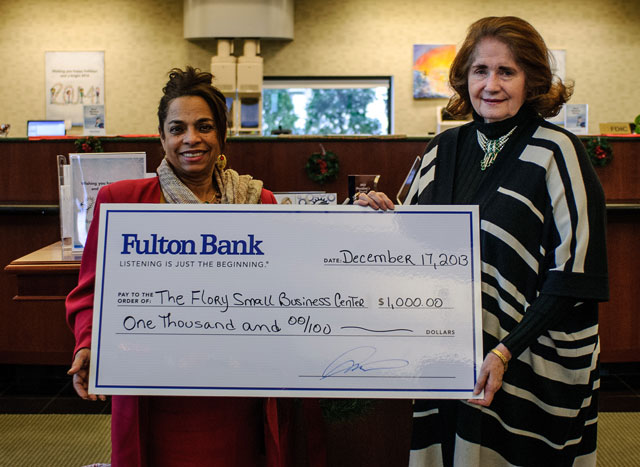Nury Mena, Branch Manager for Fulton's Manassas Branch, presented the check to Flory Small Business Centre President Linda Decker.